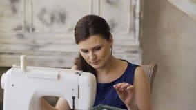 El diseñador de la ropa y la mujer jovenes de la costurera trabajan con la máquina de coser en estudio del sastre metrajes