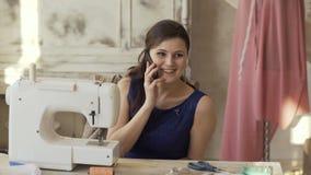 El diseñador joven de la ropa y la máquina de coser cercana de la mujer de la costurera habla el teléfono que sonríe en estudio metrajes