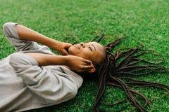 El disfrute de la música del adolescente afroamericano La chica joven está poniendo en la hierba Fotos de archivo