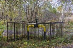 El dispositivo de fijación del gaseoducto que pasaba en la madera y trajo el exterior, protegido por una cerca para la seguridad  fotografía de archivo
