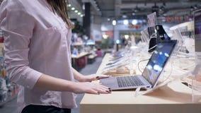 El dispositivo de la tecnología, cliente hermoso de la mujer joven considera nuevo netbook moderno en tienda de la electrónica almacen de metraje de vídeo