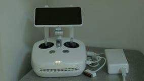 El dispositivo de los mandos de vuelo de un vehículo aéreo sin tripulación está conectado con un cargador La pantalla de monitor  almacen de video