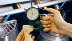 El dispositivo en manos femeninas está formando un pedazo cortado de la patata almacen de metraje de vídeo
