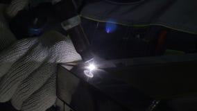El dispositivo macro de la soldadura oxiacetilénica actúa en manos en la oscuridad metrajes