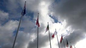 El diverso mundo señala el vuelo por medio de una bandera en astas de bandera en un fondo del cielo y de las nubes almacen de video