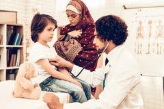 El doctor árabe Checking Heartbeat Little Boy El doctor de sexo femenino árabe Examining Little Boy Niño en el pediatra Hospital fotos de archivo libres de regalías