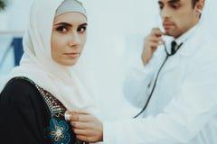 El doctor árabe Checking Heartbeat una mujer musulmán foto de archivo libre de regalías