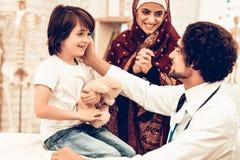 El doctor árabe Giving Toy a poco paciente lindo fotos de archivo