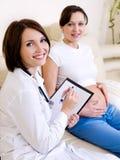 El doctor aconseja a la mujer embarazada Imagen de archivo libre de regalías