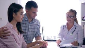 El doctor aconseja pares jovenes en una recepción en una clínica de fertilidad, planificación familiar almacen de metraje de vídeo