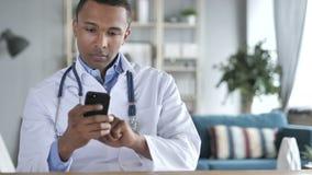 El doctor afroamericano Working en los documentos y el ordenador portátil médicos, papeleo almacen de metraje de vídeo
