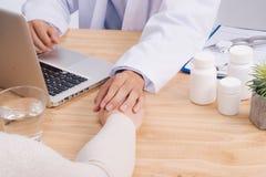 El doctor amistoso da llevar a cabo la mano paciente que se sienta en el escritorio f Fotos de archivo libres de regalías