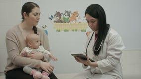 El doctor amistoso del pediatra explica algo a almacen de metraje de vídeo