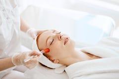El doctor aplica la máscara hidráulica del gel en la mujer antes de hacer el tratamiento del laser imagen de archivo libre de regalías