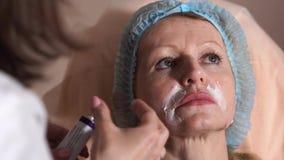 El doctor aplica un ungüento en los dobleces circumfluous para la mujer para la inyección almacen de metraje de vídeo