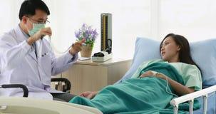 El doctor asiático examina la condición del paciente almacen de video