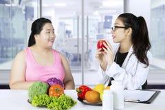 El doctor asiático muestra las comidas sanas para su paciente Imagenes de archivo