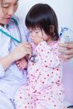 El doctor ayuda a pequeño tomar asiático respiratorio, th de la muchacha de la inhalación Imagenes de archivo