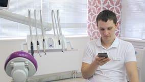 El doctor bastante joven se sienta en silla en gabinete y charla en el teléfono metrajes