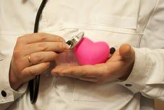 El doctor-cardiólogo escucha el corazón Foto de archivo libre de regalías