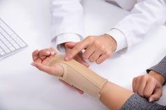 El doctor Checking Fractured Hand de una mujer fotos de archivo libres de regalías