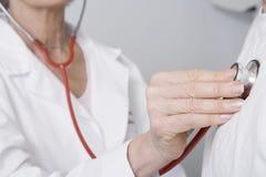 El doctor Checking Patients Heartbeat que usa el estetoscopio fotografía de archivo