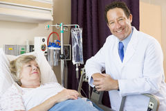 El doctor Checking Up On Patient en hospital Imágenes de archivo libres de regalías