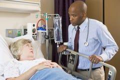 El doctor Checking Up On Patient en hospital Imagen de archivo libre de regalías