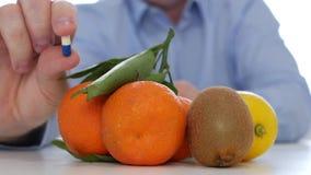 El doctor compara las frutas para consumir con el abuso de la medicina que muestra píldoras coloreadas de la vitamina almacen de video