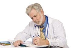 El doctor Completing Paperwork fotos de archivo libres de regalías