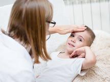 El doctor comprueba la temperatura de un muchacho que toca su frente Imagen de archivo