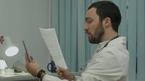 El doctor comunica por el conferention video en la PC de la tableta, discute documentos fotografía de archivo libre de regalías