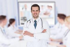 El doctor con los brazos cruzó contra la comunicación video del equipo imagenes de archivo