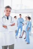 El doctor con los brazos dobló delante de su equipo médico Imagen de archivo libre de regalías