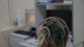 El doctor conecta los sensores electrónicos con los alambres con la cabeza paciente del ` s Tecnologías médicas progresivas almacen de video