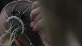 El doctor conecta los sensores electrónicos con la cabeza paciente del ` s Tecnologías médicas progresivas narc almacen de video