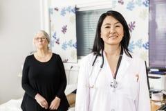 El doctor confiado Smiling While Patient que se sienta en fondo fotos de archivo