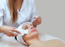 El doctor-cosmetologist hace el aparato un procedimiento de la limpieza del ultrasonido de la piel facial de una mujer hermosa, j fotos de archivo