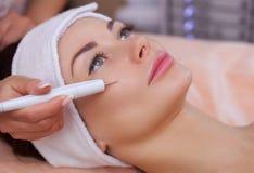 El doctor-cosmetologist hace el tratamiento del procedimiento de Couperose de la piel facial foto de archivo