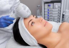 El doctor-cosmetologist hace el procedimiento Cryotherapy de la piel facial de una mujer hermosa, joven imagen de archivo