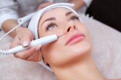 El doctor-cosmetologist hace el tratamiento del procedimiento de Couperose de la piel facial de una mujer hermosa, joven imagenes de archivo
