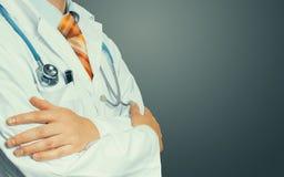 El doctor Crosses His Arms sobre su pecho en fondo gris Concepto de la medicina de la atención sanitaria foto de archivo libre de regalías
