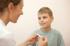 El doctor da al niño pequeño del termómetro Imagenes de archivo