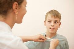 El doctor da al niño pequeño del termómetro Imagen de archivo