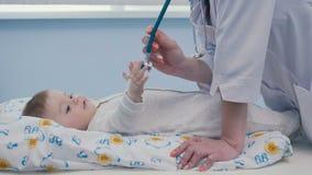 El doctor da el estetoscopio al pequeño bebé almacen de video