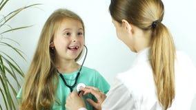 El doctor da un estetoscopio a la muchacha y ella escucha el golpeo de su corazón almacen de video