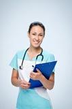 El doctor de la mujer adentro friega sostener la tableta azul para los papeles Imagen de archivo