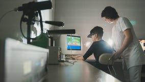 El doctor de la mujer comprueba la visión del ` s del niño con la ayuda de los vidrios de la realidad virtual del stereovideo Fotos de archivo libres de regalías