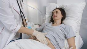 El doctor de la mujer con los guantes palpó el abdomen del paciente en el hospital almacen de video
