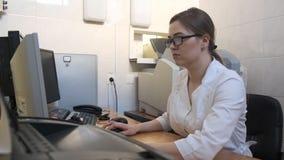 El doctor de la mujer conduce la m?quina de radiograf?a m?dica en el laboratorio de diagn?stico del hospital para la muchacha almacen de video